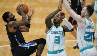 Brooklyn Nets guard Kyrie Irving shoots over Charlotte Hornets forward Gordon Hayward, right, and guard Terry Rozier during the first half of an NBA basketball game in Charlotte, N.C., Sunday, Dec. 27, 2020. (AP Photo/Chris Carlson)