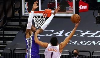 Phoenix Suns guard Devin Booker, right, goes to the basket against Sacramento Kings center Richaun Holmes during the first quarter of an NBA basketball game in Sacramento, Calif., Saturday, Dec. 26, 2020. (AP Photo/Rich Pedroncelli)