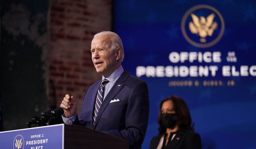 President-elect Joe Biden speaks at The Queen theater, Monday, Dec. 28, 2020, in Wilmington, Del. Vice President-elect Kamala Harris listens at right. (AP Photo/Andrew Harnik)