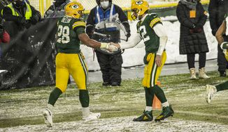 Green Bay Packers quarterback Aaron Rodgers (12) congratulates Green Bay Packers running back A.J. Dillon (28) on his touchdown during an NFL football game, Sunday, Dec 27. 2020, between the Tennessee Titans and Green Bay Packers in Green Bay, Wis. (AP Photo/Jeffrey Phelps)