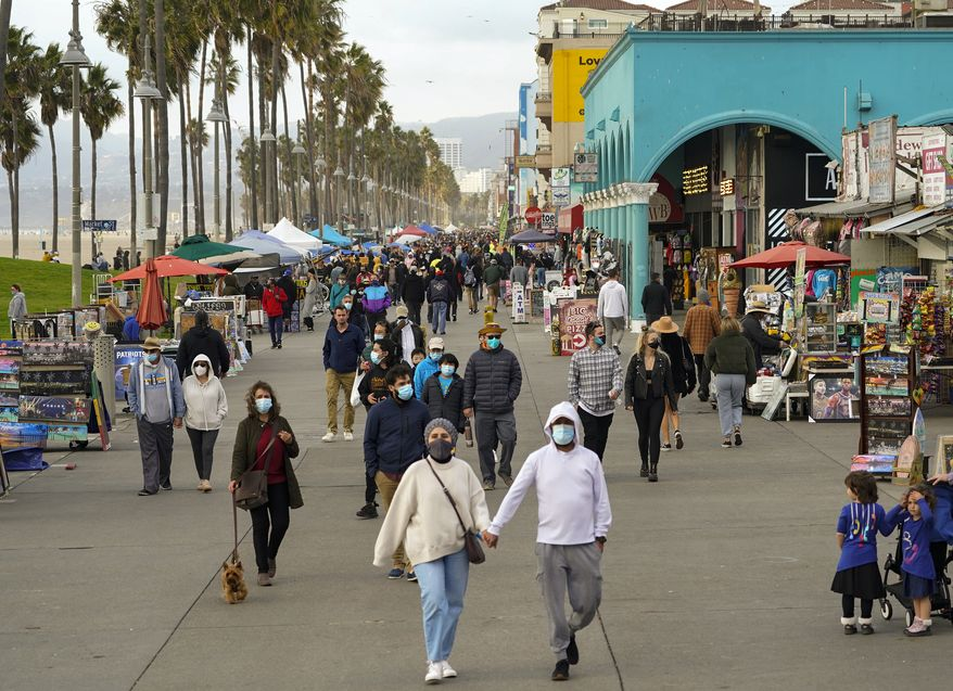 People stroll on the Venice Beach Boardwalk in Los Angeles, Sunday, Dec. 27, 2020. In Los Angeles County, the nation's most populous, county estimates show that about 1 in 95 people are contagious with the coronavirus. (AP Photo/Damian Dovarganes)