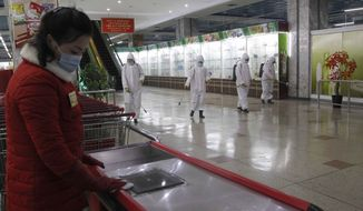 Staff of the Pyongyang Department Store No. 1 disinfect the store before it opens in Pyongyang, North Korea Monday, Dec. 28, 2020. (AP Photo/Jon Chol Jin)