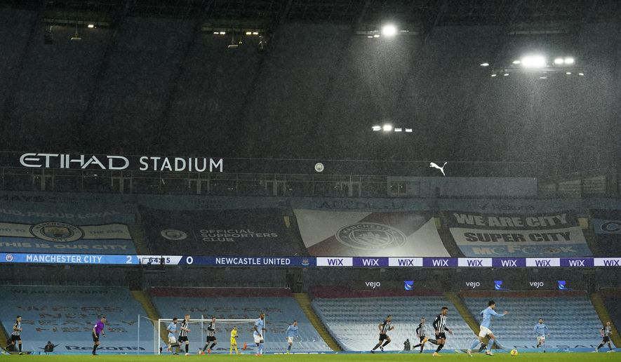 Players in the torrential rain during the English Premier League soccer match between Manchester City and Newcastle United at the Etihad stadium in Manchester, Saturday, Dec. 26, 2020. (AP Photo/Dave Thompson, Pool)