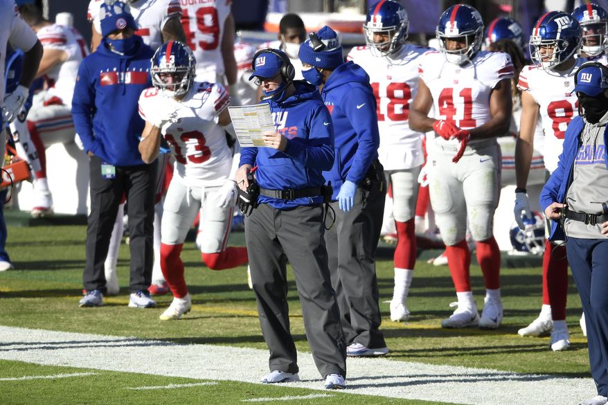 New York Giants offensive coordinator Jason Garrett, center, looks on during the first half of an NFL football game against the Baltimore Ravens, Sunday, Dec. 27, 2020, in Baltimore. (AP Photo/Nick Wass)