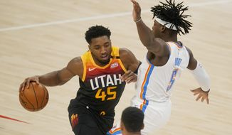 Utah Jazz guard Donovan Mitchell (45) drives against Oklahoma City Thunder guard Luguentz Dort (5) during the first half of an NBA basketball game in Oklahoma City, Monday, Dec. 28, 2020. (AP Photo/Sue Ogrocki)