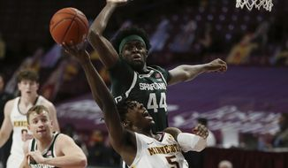 Minnesota's Marcus Carr (5) goes to the basket against Michigan State's Gabe Brown (44) during the first half of an NCAA college basketball game Monday, Dec. 28, 2020, in Minneapolis. (AP Photo/Stacy Bengs)