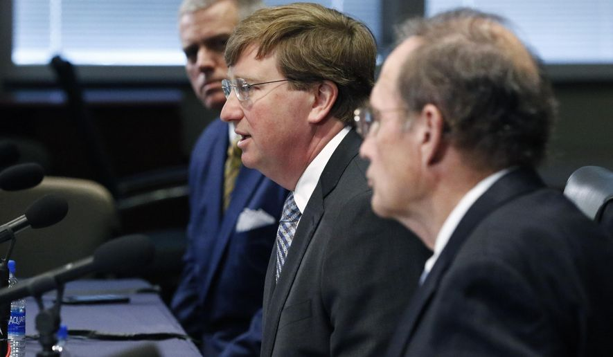 FILE - In this May 7, 2020 file photo, Gov. Tate Reeves, center, speaks of how he and House Speaker Philip Gunn, R-Clinton, left, and fellow Republican Lt. Gov. Delbert Hosemann, right, are working on a deal about how to spend $1.2 billion in CARES Act funds, in Jackson, Miss. Although party mates, Reeves went from lieutenant governor to governor and Hosemann from secretary of state to lieutenant governor it did not prevent Hosemann and the third-term House speaker Gunn from going to court to challenge Reeves' partial veto of the state budget bill. Additionally, the Legislature passed a bill that striped Reeves of sole spending authority over the CARES Act funds. (AP Photo/Rogelio V. Solis, File)