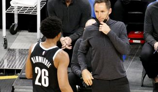 Brooklyn Nets head coach Steve Nash, right, talks with Spencer Dinwiddie during the first half of an NBA preseason basketball game against the Boston Celtics, Friday, Dec. 18, 2020, in Boston. (AP Photo/Mary Schwalm)