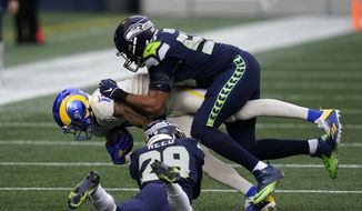 Los Angeles Rams wide receiver Josh Reynolds (11) is tackled by Seattle Seahawks free safety D.J. Reed (29) and linebacker K.J. Wright (50) during the first half of an NFL football game, Sunday, Dec. 27, 2020, in Seattle. (AP Photo/Elaine Thompson) **FILE**