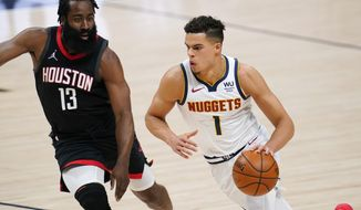 Denver Nuggets forward Michael Porter Jr., right, drives as Houston Rockets guard James Harden defends during the first half of an NBA basketball game Monday, Dec. 28, 2020, in Denver. (AP Photo/David Zalubowski)