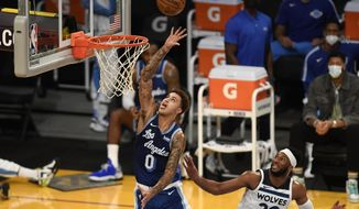 Los Angeles Lakers forward Kyle Kuzma, left, shoots past Minnesota Timberwolves guard Josh Okogie during the first half of an NBA basketball game in Los Angeles, Sunday, Dec. 27, 2020. (AP Photo/Kyusung Gong)