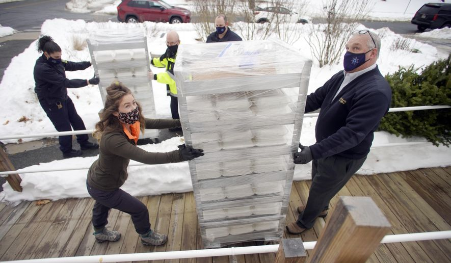 Sheriff Tom Bowlerand his daughter Meghan deliver hot meals to the Christian Center helping the Civitan Club of the Berkshires on Thursday, Dec. 24, 2020 in Pittsfield, Mass. The hot meals were prepared at the The Berkshire County Sheriff's Office. (Ben Garver/The Berkshire Eagle via AP)