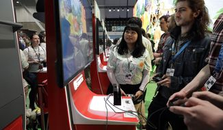 FILE - Visitors to the Pax East conference play the new Nintendo Switch video game Animal Crossing, Thursday, Feb. 27, 2020, in Boston. Thousands of gaming enthusiasts attended the Pax East conference that opened in Boston, Thursday. (AP Photo/Steven Senne)