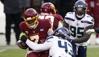 Washington Football Team quarterback Dwayne Haskins (7) is sacked by Seattle Seahawks defensive end Carlos Dunlap (43) during an NFL football game between the Seattle Seahawks and the Washington Football Team, Sunday, Dec. 20, 2020, in Landover, Md. (AP Photo/Mark Tenally) ** FILE**