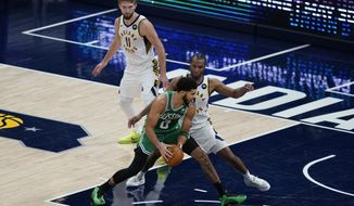 Boston Celtics' Jayson Tatum (0) goes to the basket against Indiana Pacers' T.J. Warren, right, during the second half of an NBA basketball game Tuesday, Dec. 29, 2020, in Indianapolis. (AP Photo/Darron Cummings)