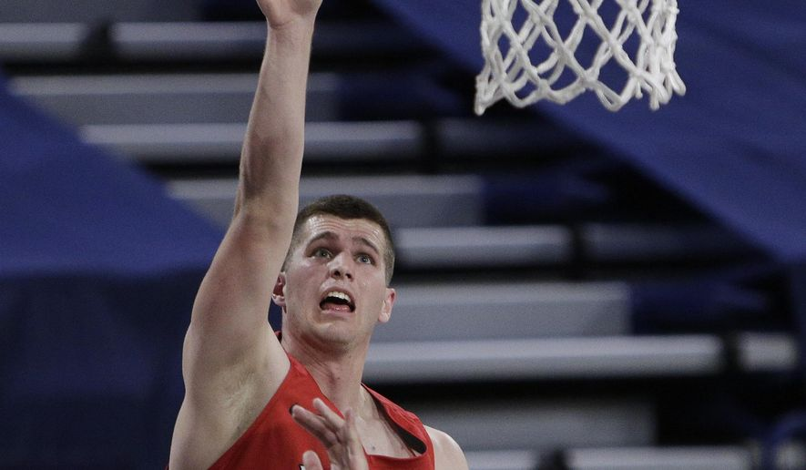 Dixie State forward Hunter Schofield, left, shoots over Gonzaga guard Andrew Nembhard during the first half of an NCAA college basketball game in Spokane, Wash., Tuesday, Dec. 29, 2020. (AP Photo/Young Kwak)