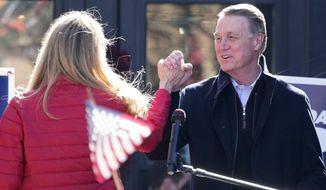 Sen. David Perdue, R-Ga., and Sen. Kelly Loeffler, R-Ga., clasp hands during a campaign rally, Monday Dec. 21, 2020, in Milton, Ga. (AP Photo/John Bazemore)