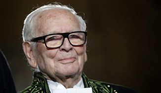 In this Nov. 30, 2016, file photo, French fashion designer Pierre Cardin acknowledges applause after a show to mark 70 years of his creations, in Paris. France's Academy of Fine Arts says famed fashion designer Cardin has died at 98. (AP Photo/Christophe Ena, File)