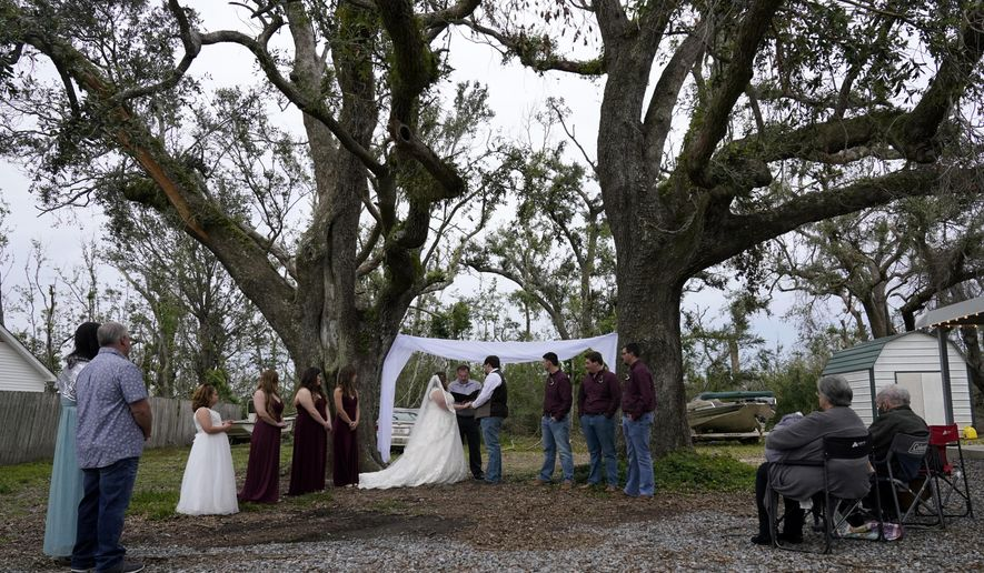 Emily and Taylor Pascale exchange their wedding vows outside the home of Taylor's parents, Friday, Dec. 4, 2020, in Grand Lake, La., which was heavily damaged from Hurricanes Laura and Delta. (AP Photo/Gerald Herbert)