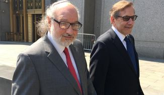 In this July 22, 2016, file photo convicted spy Jonathan Pollard, left, with his lawyer, Eliot Lauer, leaves federal court in New York following a hearing. Israeli media say Pollard, who spent 30 years in U.S. prison for spying for Israel, has landed in the country with his wife.  The U.S. Justice Department announced in November that Pollard had completed his parole, clearing the way for him to move to Israel 35 years after he was arrested. Pollard has said it was his dream to move to the country.(AP Photo/Larry Neumeister, File)