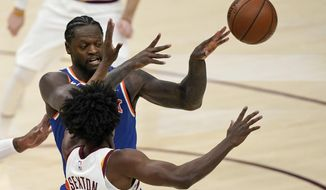 New York Knicks' Julius Randle, back, passes the ball away from Cleveland Cavaliers' Collin Sexton during the second half of an NBA basketball game Tuesday, Dec. 29, 2020, in Cleveland. The Knicks won 95-86. (AP Photo/Tony Dejak)