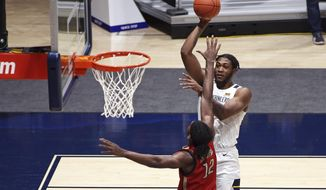 West Virginia forward Derek Culver (1) shoots while defended by Northeastern forward Alex Nwagha (12) during the first half of an NCAA college basketball game Tuesday, Dec. 29, 2020, in Morgantown, W.Va. (AP Photo/Kathleen Batten)