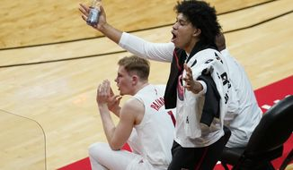 Rutgers guard Ron Harper Jr., who sat out the game with an ankle injury, yells from the bench as a Purdue player shoots a free throw during the second half of an NCAA college basketball game Tuesday, Dec. 29, 2020, in Piscataway, N.J. Rutgers forward Oskar Palmquist is at left. (AP Photo/Kathy Willens)
