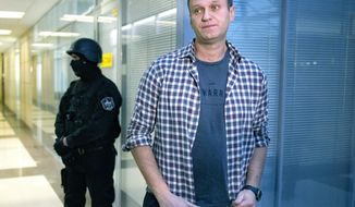 FILE- In this Dec. 26, 2019, file photo, Russian opposition leader Alexei Navalny speaks to the media in front of a security officer standing guard at the Foundation for Fighting Corruption office in Moscow, Russia. Russian authorities on Tuesday Dec. 29, 2020, ramped up pressure on top Kremlin critic Alexei Navalny, leveling new charges of fraud against him. (AP Photo/Alexander Zemlianichenko, File)
