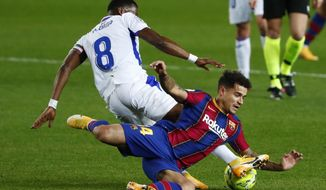 Eibar's Pape Diop, left, challenges Barcelona's Philippe Coutinho during the Spanish La Liga soccer match between Barcelona and Eibar at the Camp Nou stadium in Barcelona in Barcelona, Spain, Tuesday, Dec. 29, 2020. (AP Photo/Joan Monfort)