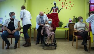 A nurse administers a COVID-19 vaccine to Josepha Delmotte, 102 years old, center, at La Bonne Maison de Bouzanton care home in Mons, Belgium, Monday, Dec. 28, 2020. The vaccine, developed by BioNTech and Pfizer, was transported from a hospital in Leuven to the residential care home on Monday, as Belgium begins its vaccination program starting with the most vulnerable. Also being vaccinated, nurse Marie-Catherine Van Broeck, second right, and Toni Agostinelli, left, who both work at the home. (AP Photo/Francisco Seco, Pool)