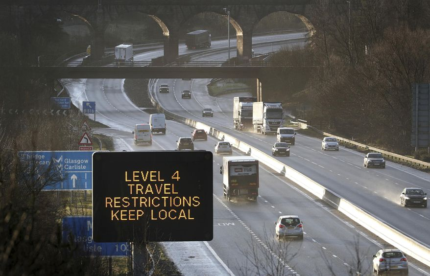 In this file photo, a traffic information board advises drivers to keep their travel to local trips because of coronavirus Level 4 restrictions, as traffic moves along the M80 motorway near Banknock, Scotland, Tuesday Dec. 29, 2020. Scotland has imposed more severe COVID-19 lockdown restrictions for several weeks. (Andrew Milligan/PA via AP) **FILE**