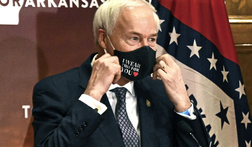 FILE - In this July 20, 2020 file photo, Gov. Asa Hutchinson removes his mask before a briefing at the state capitol in Little Rock.  State lawmakers across the country will be convening in 2021 with the continuing COVID-19 pandemic rippling through much of their work and even affecting the way they work. After 10 months of emergency orders and restrictions from governors and local executive officials, some state lawmakers are eager to reassert their power over statewide decisions shaping the way people shop, work, worship and attend school (Staci Vandagriff/The Arkansas Democrat-Gazette via AP)