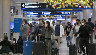 Travelers wearing protective face masks walk through Concourse D at Miami International Airport, Monday, Dec. 28, 2020, in Miami. (David Santiago/Miami Herald via AP) ** FILE **