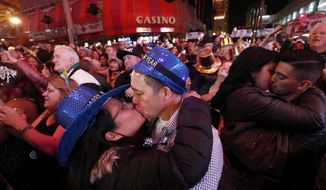 """FILE - In this Jan. 1, 2018, file photo, newlyweds Alison and Kenny Finchum, lower left, of Tulsa, Okla., kiss just after midnight during a New Year's party at the Fremont Street Experience in downtown Las Vegas. Plans for a 14,000-person New Year's Eve street party at canopied casino-mall in Las Vegas are facing pushback from state and local officials, who worry Nevada hospitals may not be able to withstand a potential """"superspreader"""" event. (Steve Marcus/Las Vegas Sun via AP, File)"""
