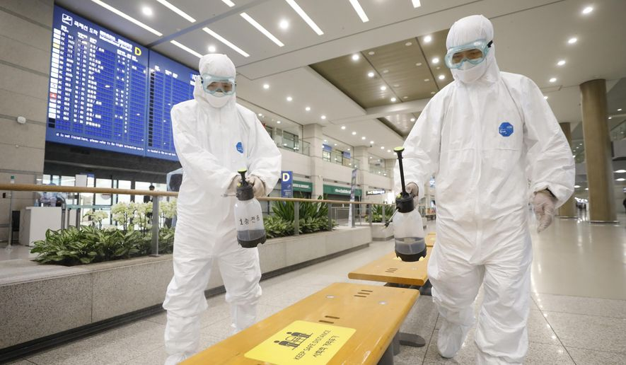 Workers wearing protective gears disinfect chairs as a precaution against the coronavirus at the arrival hall of the Incheon International Airport in Incheon, South Korea, Tuesday, Dec. 29, 2020. South Korea says 40 more coronavirus patients have died in the past 24 hours, the highest daily fatalities since the pandemic began, as the country is grappling with surging cases in recent weeks. (Ko Seung-min/Newsis via AP)