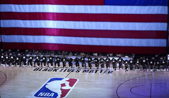 FILE - Members of the Orlando Magic and Brooklyn Nets kneel around a Black Lives Matter logo during the national anthem before the start of an NBA basketball game in Lake Buena Vista, Fla., in this Friday, July 31, 2020, file photo. As the NBA neared its restart in late July, its players vowed to keep the calls for social justice reform at the forefront in the wake of the deaths of George Floyd and Breonna Taylor.(AP Photo/Ashley Landis, Pool, File)