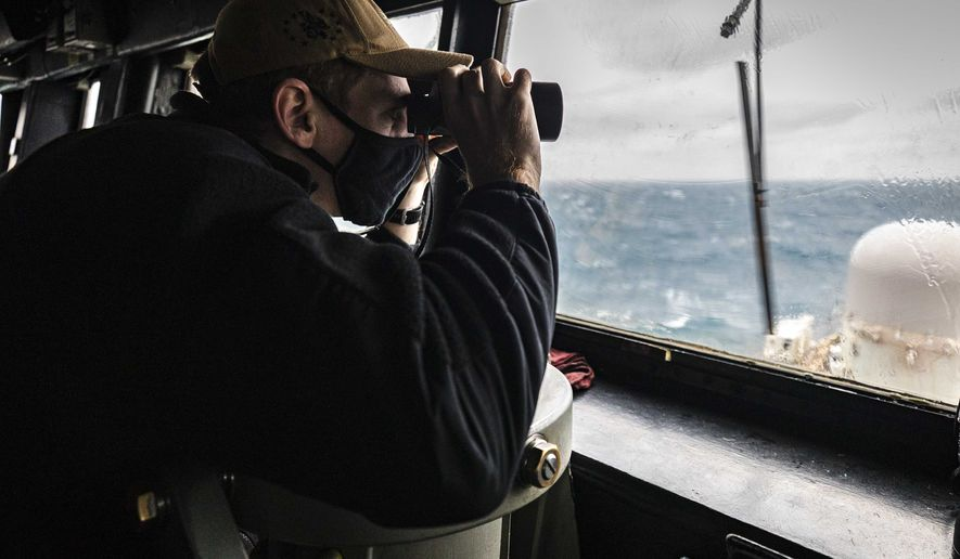 In this file photo provided by U.S. Navy, Ensign Grayson Sigler, from Corpus Christi, TX., scans the horizon while standing watch in the pilot house as guided-missile destroyer USS John S. McCain conducts routine underway operations in support of stability and security for a free and open Indo-Pacific, at the Taiwan Strait, Wednesday, Dec. 30, 2020. China accused the U.S. of staging a show of force by sailing two Navy warships through the Taiwan Strait on Thursday morning. The Navy said the Arleigh Burke-class guided missile destroyers USS John S. McCain and USS Curtis Wilbur conducted a routine Taiwan Strait transit in accordance with international law. (Mass Communication Specialist 2nd Class Markus Castaneda/U.S. Navy via AP)  **FILE**
