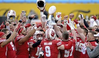 Wisconsin players hoist the trophy following victory over Wake Forest in the Duke's Mayo Bowl NCAA college football game at Bank of America Stadium in Charlotte, N.C., Wednesday, Dec. 30, 2020. (Jeff Siner/The News & Observer via AP)