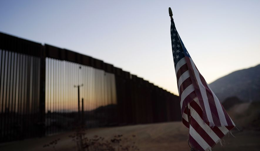 In this Sept. 24, 2020, photo a flag sits just north of a new section of the border structure near Tecate, Calif. The Trump administration sought to halt migrants from crossing the southwest border through measures that included forcing people seeking asylum to do so in Mexico or Central America and building about 450 miles of wall. (AP Photo/Gregory Bull) **FILE**