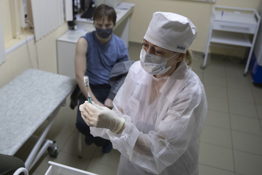 A medical worker, right, prepares a shot of Russia's Sputnik V coronavirus vaccine in Moscow, Russia, Wednesday, Dec. 30, 2020. Russia's Health Ministry has allowed a domestically designed coronavirus vaccine to be given to people older than 60. Sputnik V's developers have said data suggests the vaccine was 91% effective, a conclusion based on 78 coronavirus infections among nearly 23,000 participants. That's far fewer cases than Western drugmakers have accumulated during final testing before analyzing how well their vaccine candidates worked. (AP Photo/Pavel Golovkin)