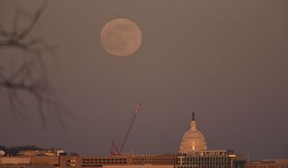This Tuesday, Dec. 29, 2020, photo shows the rising full moon above the U.S. Capitol in Washington, D.C. (AP Photo/Kevin S. Vineys)