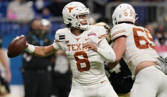 Texas quarterback Casey Thompson (8) looks for a receiver during the second half of the team's Alamo Bowl NCAA college football game against Colorado, Tuesday, Dec. 29, 2020, in San Antonio. (AP Photo/Eric Gay)