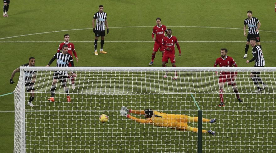Liverpool's goalkeeper Alisson dives full length to make a save from a header by -Newcastle's Ciaran Clark, at right, during the English Premier League soccer match between Newcastle United and Liverpool at St James' Park stadium in Newcastle, England, Wednesday, Dec. 30, 2020. (AP Photo/Scott Heppell)
