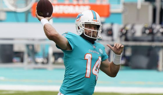 Miami Dolphins quarterback Ryan Fitzpatrick (14) warms up before an NFL football game against the Cincinnati Bengals, Sunday, Dec. 6, 2020, in Miami Gardens, Fla. The Miami Dolphins need a good game Sunday to ensure they get to keep playing, and that's especially true for Tua Tagovailoa. Coach Brian Flores has benched Tagovailoa twice in the fourth quarter, including last week at Las Vegas, when backup quarterback Ryan Fitzpatrick helped Miami overcome a pair of deficits in the final 10 minutes. (AP Photo/Wilfredo Lee)