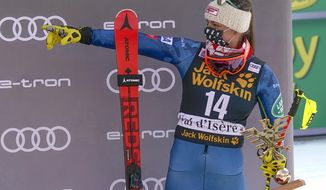 United States' Breezy Johnson holds the trophy after finishing third in a alpine ski, women's World Cup downhill, in Val d'Isere, France, Saturday, Dec.19, 2020. (AP Photo/Giovanni Auletta)