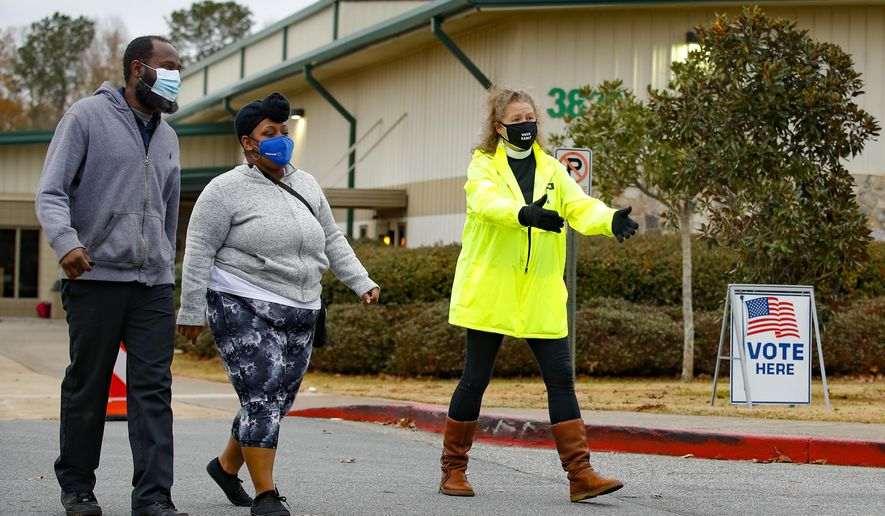 An Election Defender volunteer directs voters to an area where they can get free hand sanitizer and masks, during early voting for the Senate runoff election, at a recreation center Thursday, Dec. 17, 2020, in Powder Springs, Ga. (AP Photo/Todd Kirkland)