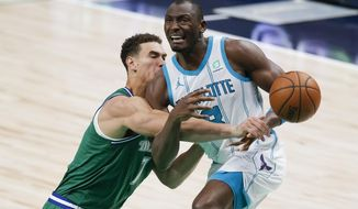 Dallas Mavericks forward Dwight Powell (7) knocks the ball away from Charlotte Hornets forward Bismack Biyombo (8) during the second half of an NBA basketball game, Wednesday, Dec. 30, 2020, in Dallas. (AP Photo/Brandon Wade)