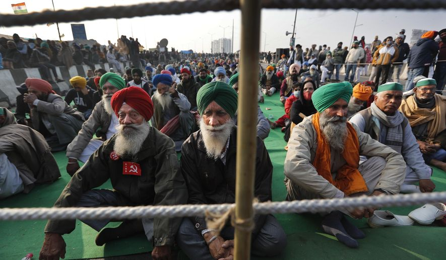 Indian farmers listen to a fellow farmer speak as they block a highway in protest against new farm laws at the Delhi-Uttar Pradesh state border, on the outskirts of New Delhi, India, Wednesday, Dec. 30, 2020. Protesting farmers fear the government will stop buying grain at minimum guaranteed prices and corporations will then push down prices. The government says the three laws approved by Parliament in September will enable farmers to market their produce and boost production through private investment. (AP Photo/Manish Swarup)