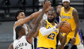 Los Angeles Lakers forward LeBron James (23) is pressured by San Antonio Spurs guard Lonnie Walker IV (1) and guard Keldon Johnson during the first half of an NBA basketball game in San Antonio, Wednesday, Dec. 30, 2020. (AP Photo/Eric Gay)
