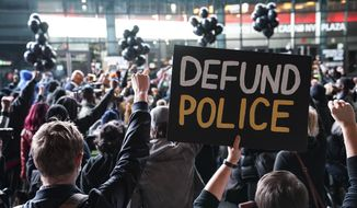 In this Wednesday, Oct. 14, 2020, file photo, a protester holds a sign that reads 'Defund Police'during a rally for the late George Floyd outside Barclays Center, in New York. (AP Photo/John Minchillo, File)  **FILE**